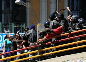 Demonstrators clash with riot police on a pedestrian bridge during a rally protest by people with physical disabilities demanding the government for a monthly subsidy, in La Paz