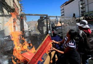 Demonstrators try to set fire to a police barricade, during a protest by people with physical disabilities demanding the government to increase their monthly disability subsidy, in La Paz