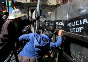 Demonstrators try to get past a police barricade in La Paz