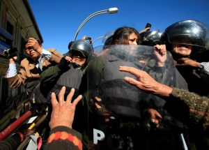 Riot police officers try to stop demonstrators with physical disabilities during a rally protest demanding the government for a monthly subsidy, in La Paz