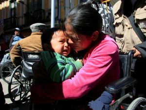 A woman with a physical disability and a child cry during a rally protest demanding the government for a monthly subsidy, in La Paz