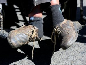 The feet of a man with a physical disability are pictured during a protest rally demanding the government for a monthly subsidy, in La Paz