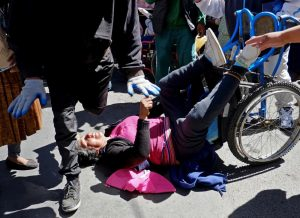 A demonstrator with physical disability falls from a wheelchair during a protest to demand that the government increase the monthly disability subsidy in La Pazwith physical disabilities