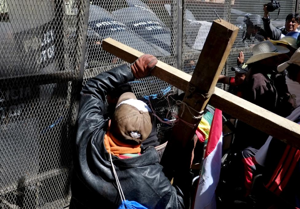 Demonstrators with physical disabilities try to get past a fence during a protest to demand that the government increase their monthly disability subsidy in La Paz