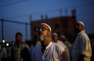 Muslim men look towards the sky to spot the crescent moon, on the eve of the holy fasting month of Ramadan, at the Jama Masjid (Grand Mosque) in the old quarters of Delhi, India, June 6, 2016. REUTERS/Adnan Abidi