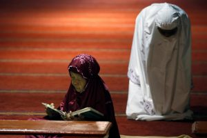 A Muslim woman (L) reads the Koran as other pray during the first day of the holy fasting month of Ramadan at Istiqlal mosque in Jakarta, Indonesia June 6, 2016. REUTERS/Beawiharta